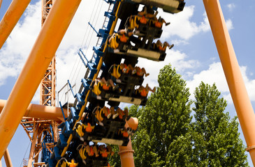 roller coaster view against summer sky with passengers
