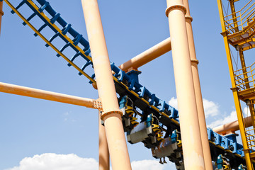 roller coaster view against summer sky with passengers hanging