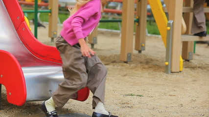 Two little children sliding on chute in playground