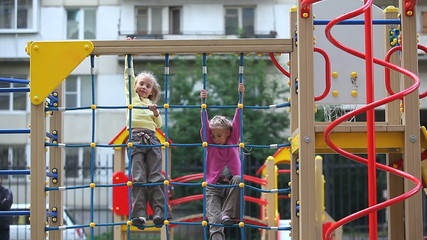 Two little girls climbing on playground net