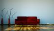 Wohndesign - rotes Sofa vor weisser Wand