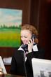 lächelnde mitarbeiterin im hotel telefoniert