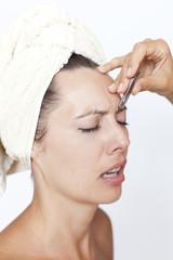Frau hat Schmerzen beim Augenbrauen zupfen