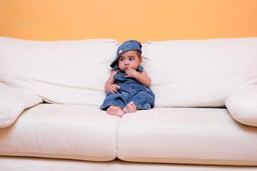 neonato con tuta in jeans sul divano