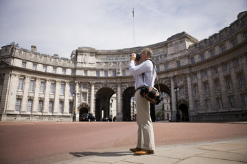 A man standing by Admiralty Arch, taking a photograph