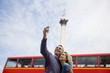A couple taking a photograph of themselves near Nelson's column