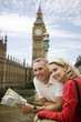 A middle-aged couple standing near the Houses of Parliament