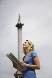 A woman standing in Trafalgar Square, looking at a map