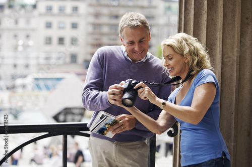A middle-aged couple looking at photographs on their camera