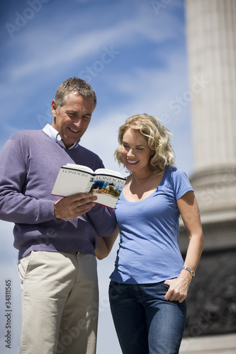 A middle-aged couple looking at a guidebook
