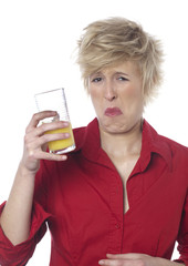 jeune femme écœurée par un verre de jus d'oranges