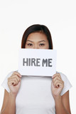 Woman holding placard with text 'hire me'