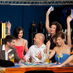 happy caucasian friends playing blackjack in casino