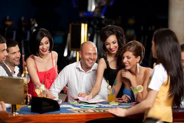 happy caucasian friends playing blackjack in casino