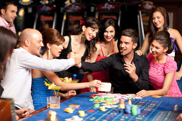 happy caucasian friends playing roulette in casino