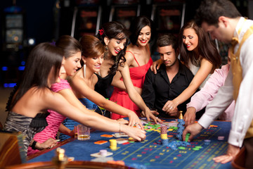 smiling people and dealer playing roulette