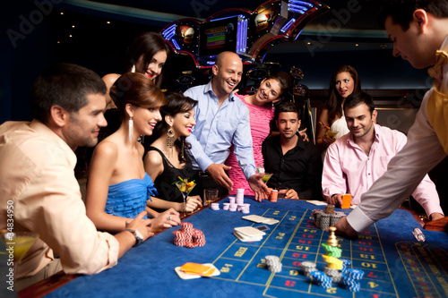 canvas print picture happy friends playing roulette in a casino