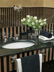dettaglio di bagno con top in marmo nero e vaso di tulipani