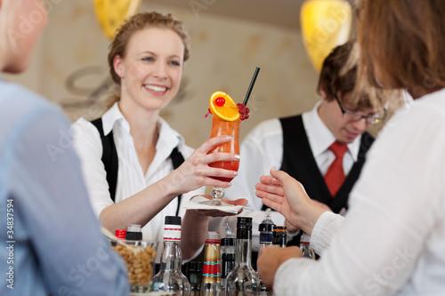 Leinwanddruck Bild gast bekommt fruchtigen cocktail