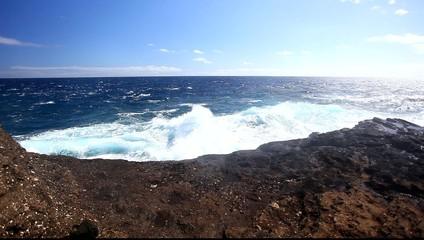 Ocean waves crash over a rocky shore.