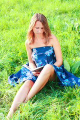 Young woman sitting in grass reading book