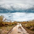 Flooded road in prairie and dramatic sky