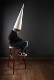 Child wearing a dunce cap