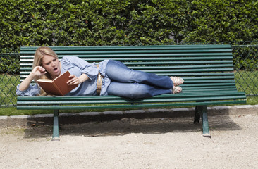 Jeune femme lisant sur un banc