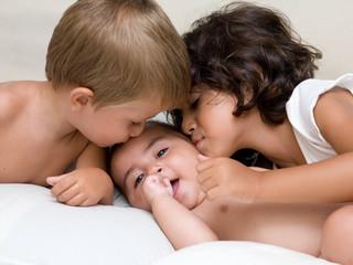 bambini che baciano un neonato