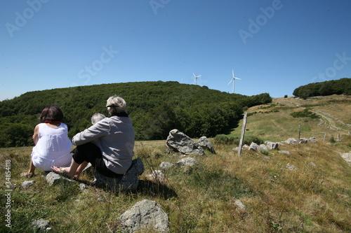 promeneurs au pied d'éoliennes en campagne