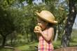 Jeune fille de profil croquant dans une pomme