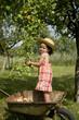 Jeune fille debout dans une brouette