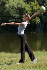 Девочка выполняет гимнастическое упражнение с мячом на природе.