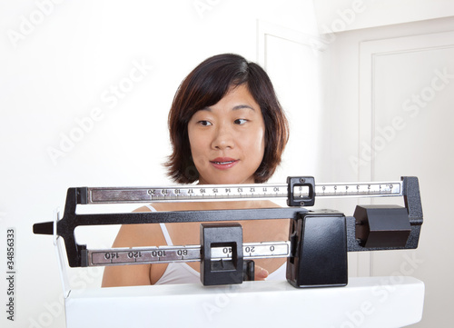 Woman Weighing on Medical Weight Scale