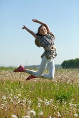 teenager girl jumps at meadow
