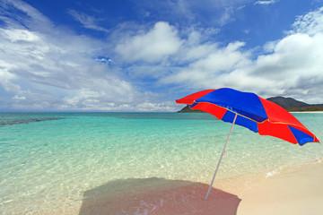 透明な海と波打ち際に立つビーチパラソル