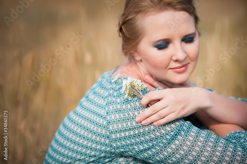 Beautiful woman relaxing in the straw in field