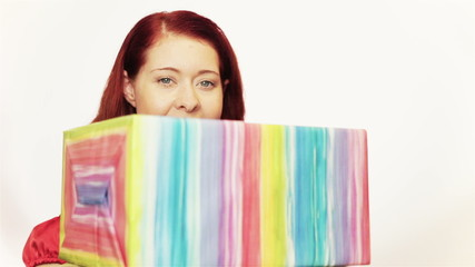 Redhaired woman behind christmas gifts