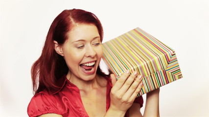 Excited woman shaking christmas gift