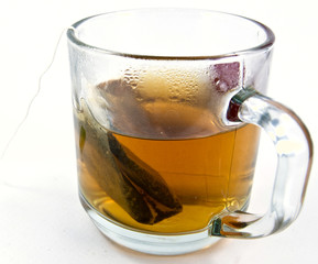 A tea bag in the cup with hot water.