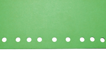 Green paper with circular holes, isolated on white.