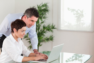 Manager and his secretary working with a laptop