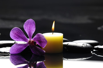 burning spa candles with pink orchid and stones reflection