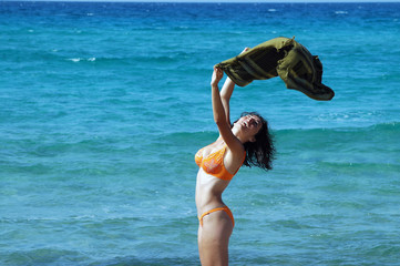 Beautiful young woman on the beach with a colored tissue
