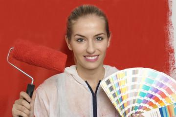 Frau mit Farbfächer und Farbrolle vor roter Wand