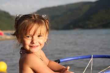portrait de petite fille souriante au bord de l'eau