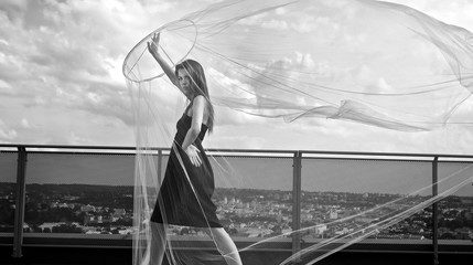 Romantic beauty with umbrella on a skyscraper roof.