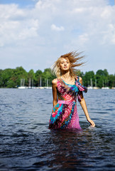 Beautiful blond model standing on water.