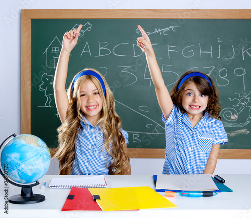 clever students in classroom raising hand