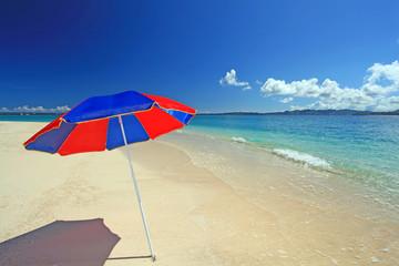 真っ白な砂浜に立つビーチパラソル